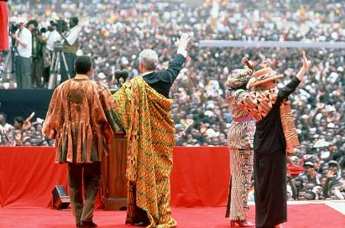 In 1998 United States president Bill Clinton and first lady Hillary Rodham Clinton made a six-nation tour of Africa, the most extensive visit to Africa ever undertaken by a sitting U.S. president. At his first stop, in Ghana, Clinton was greeted by a crowd hundreds of thousands strong. Here, draped in a traditional Ghanaian kente cloth, President Clinton, center, waves to the crowd, accompanied by the first lady, far right, and Ghanaian president Jerry Rawlings left.